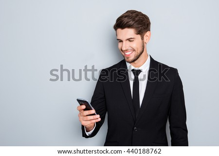 Cheerful young businessman in suit reading sms on smartphone