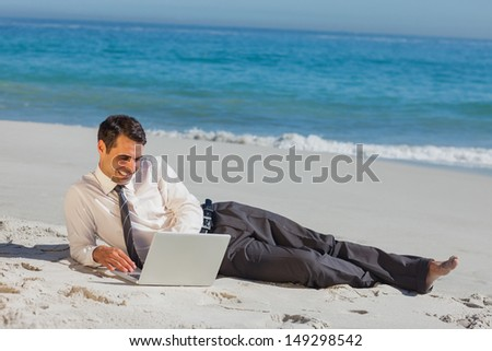 Cheerful young businessman relaxing lying on the sand with his laptop
