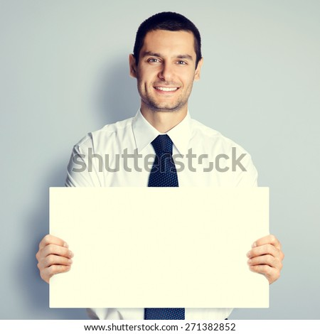 Cheerful young businessman showing blank signboard with copyspace area for text or slogan, specially toned - stock photo