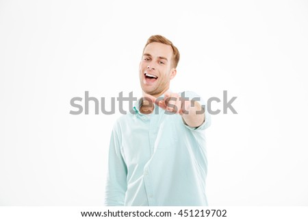 Cheerful young businessman standing and pointing on you over white background - stock photo