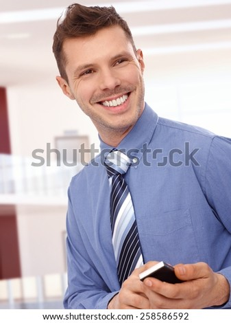 Cheerful young businessman with mobile phone at office center. Toothy smile, standing, tie, no jacket. - stock photo