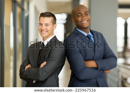 cheerful young businessmen with arms crossed in office - stock photo