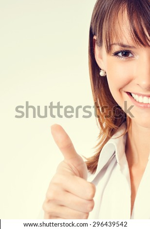 Cheerful young businesswoman in white business style clothing showing thumbs up gesture - stock photo