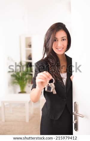 cheerful young businesswoman real estate agent holding and giving keys to a new rental house - stock photo