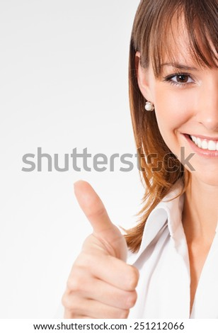 Cheerful young businesswoman showing thumbs up gesture - stock photo