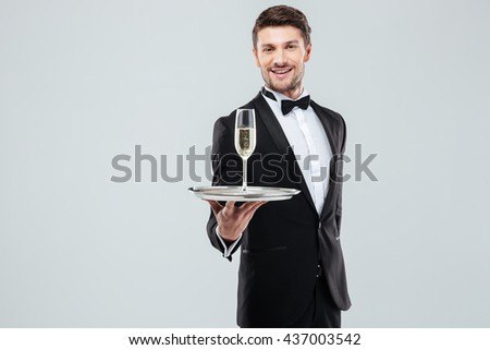 Cheerful young butler in tuxedo with bow tie standing and offering you glass of champagne over white background - stock photo