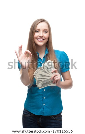 cheerful young caucasian businesswoman in blue blouse holding money and showing ok isolated on white - stock photo
