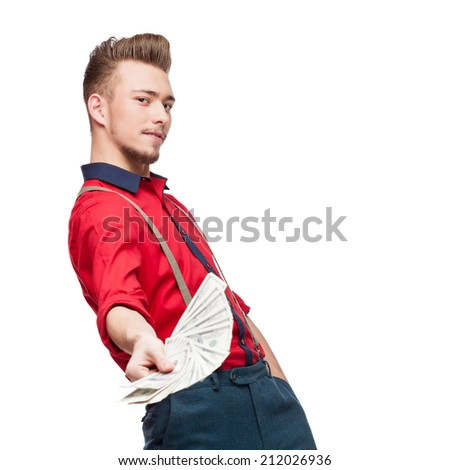 cheerful young caucasian man in red vintage clothing holding money isolated on white