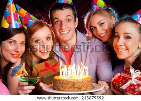 cheerful young company celebrates birthday and have a cake with candles  - stock photo