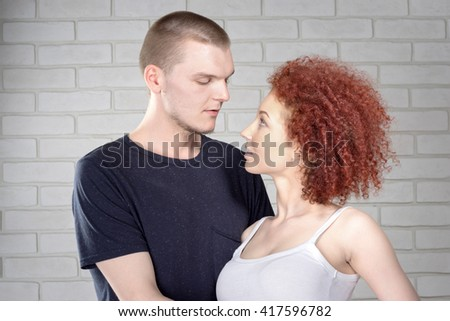 Cheerful young couple. Attractive man and woman being playful. - stock photo