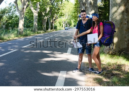 cheerful young couple backpacker hitchhiking on a roadside in summer vacation