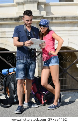 cheerful young couple backpacker traveling and sightseeing in europe during summer - stock photo