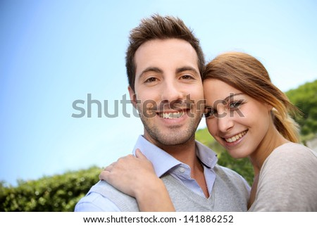 Cheerful young couple embracing each other outside - stock photo