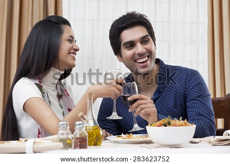 Cheerful young couple enjoying the meal at restaurant - stock photo