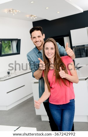 cheerful young couple happy in their new modern design house showing thumbs up - stock photo