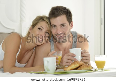 Cheerful young couple having breakfast in bed - stock photo