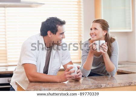 Cheerful young couple having coffee together - stock photo