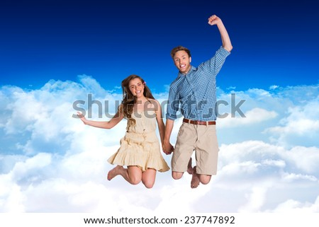 Cheerful young couple jumping against bright blue sky over clouds - stock photo