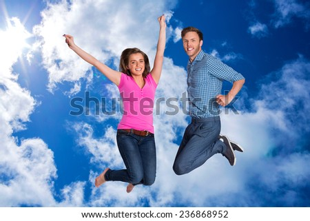 Cheerful young couple jumping against bright blue sky with clouds - stock photo