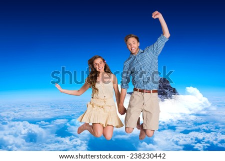 Cheerful young couple jumping against mountain peak through the clouds - stock photo