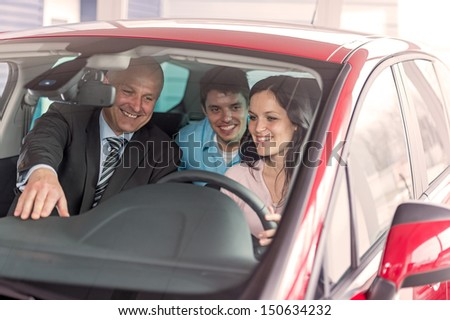 Cheerful young couple looking around in new car - stock photo