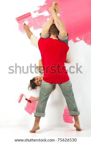 Cheerful young couple of workers painting a wall with roller arsy-versy - stock photo