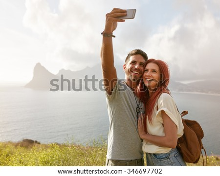 Cheerful young couple on holidays making selfie with smart phone. Young couple by the bay taking a selfie portrait with cell phone. - stock photo