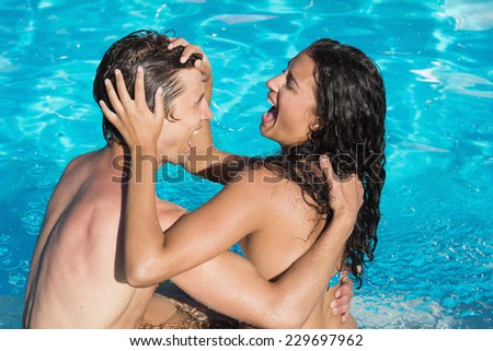 Cheerful young couple playing in swimming pool - stock photo