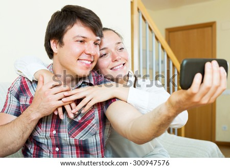 Cheerful young couple posing for a selfie at home - stock photo