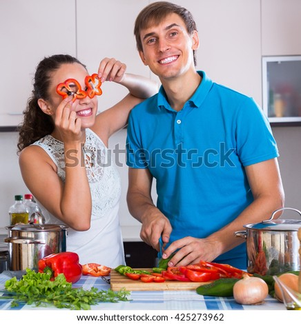 Cheerful young couple preparing dinner with vegetables together