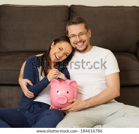 Cheerful young couple putting banknote in piggybank  - stock photo