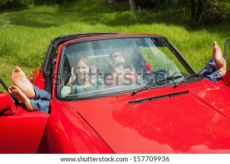 Cheerful young couple relaxing in classy cabriolet on a sunny day - stock photo