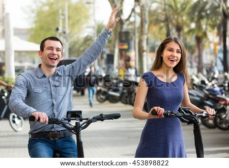 Cheerful young couple riding on electric bikes on the street and smiling - stock photo