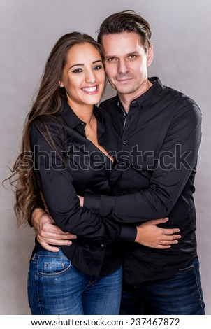 Cheerful young couple standing in the studio. - stock photo
