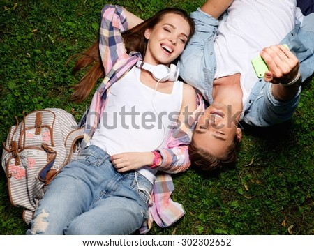 Cheerful young couple taking selfie lying on a grass in a park  - stock photo
