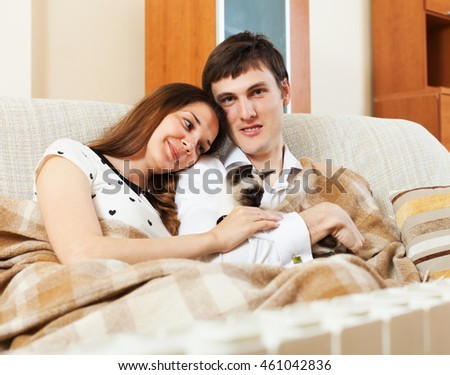 cheerful  young  couple with kitten on sofa
