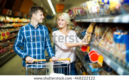 Cheerful young customers choosing bread and pastry in food shop. Focus on the woman