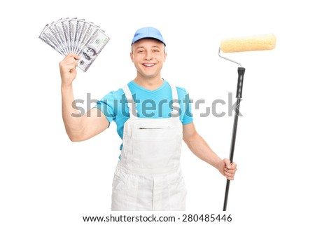 Cheerful young decorator holding a paint roller and a stack of money isolated on white background - stock photo