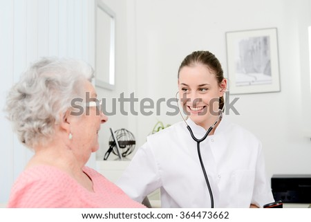 cheerful young doctor giving medical health care to an elderly woman at home - stock photo
