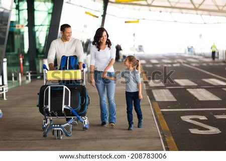 cheerful young family at airport with a trolley full of luggage  - stock photo