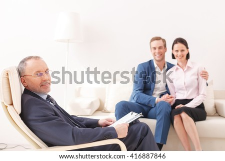 Cheerful young family is consulting a psychotherapist - stock photo
