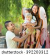 Cheerful young family of four at children's playground in summer park