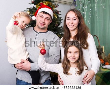 Cheerful young family of four at home with  Christmas tree at home - stock photo
