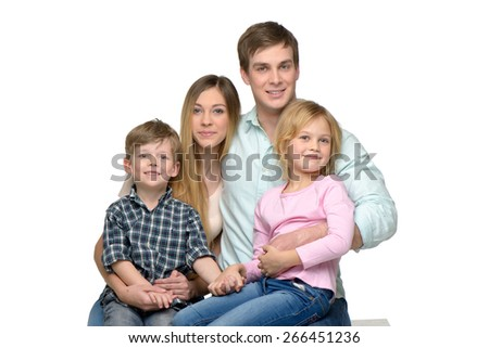 Cheerful young family of four posing. Isolated on white background. Concept for happy family - stock photo