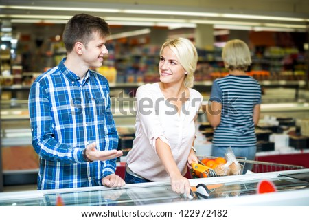 Cheerful young family standing near display with frozen food in supermarket. Focus on the woman - stock photo