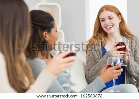 Cheerful young female friends with wine glasses enjoying a conversation on sofa at home - stock photo