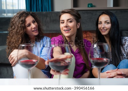 Cheerful young female friends with wine glasses enjoying a conversation on sofa at home