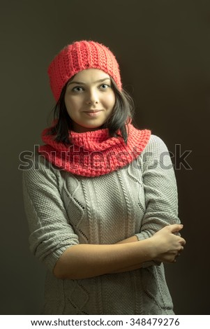 Cheerful young female in winter knitted sweater and pink scarf and hat posing with arms crossed on dark grey background - stock photo