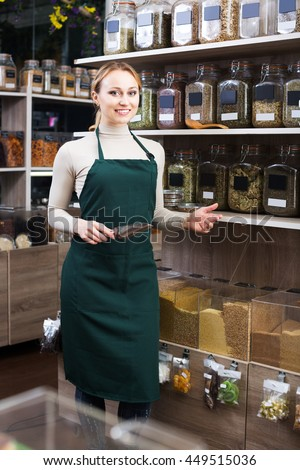 Cheerful young female seller in uniform standing in the store with ecological goods