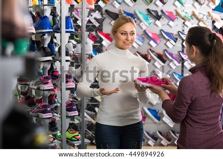 Cheerful young female seller showing an assortment of the shoes in the store